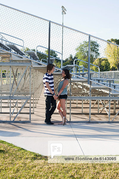 Teenage couple standing by bleachers