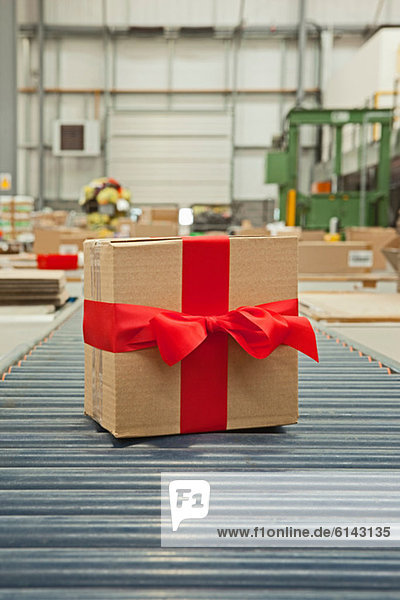 Kartonschachtel mit roter Schleife auf Förderband