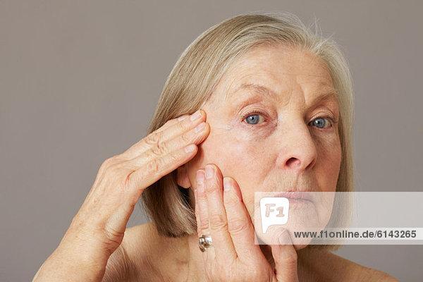 Seniorin berührt Gesicht