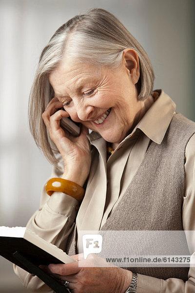 Seniorin mit Bilderrahmen am Telefon