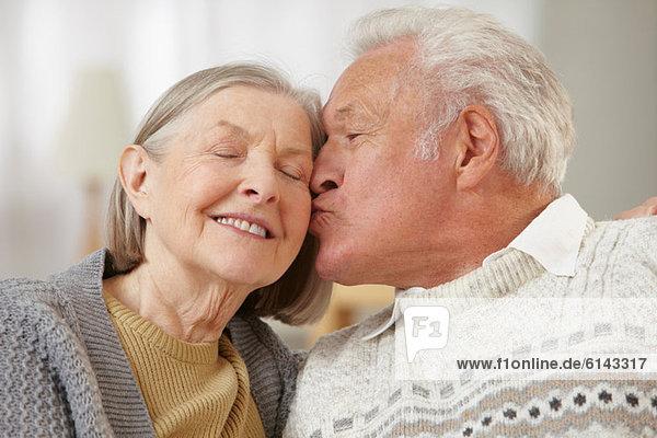 Senior Mann küsst Seniorin auf Wange
