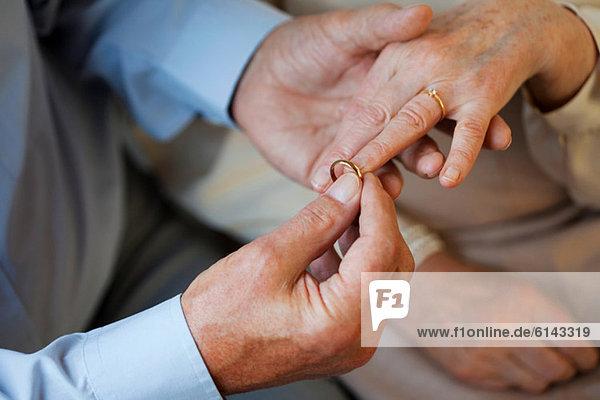Senior Mann  der den Ehering auf den Finger der Seniorin legt.