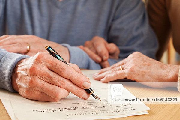 Der ältere Mann  der das Testament unterschreibt.