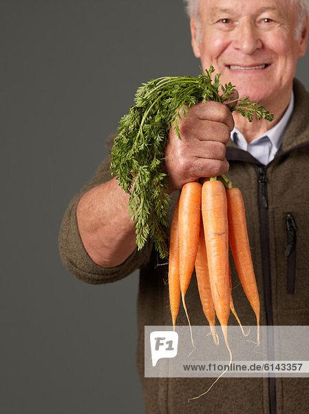 Mann mit Karotten in der Hand