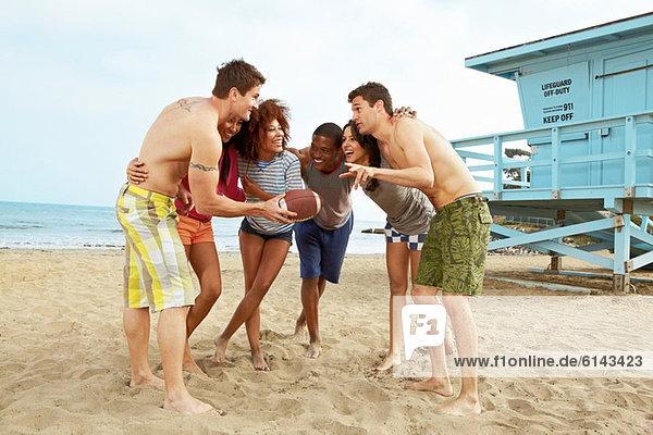Freunde am Strand spielen Rugby