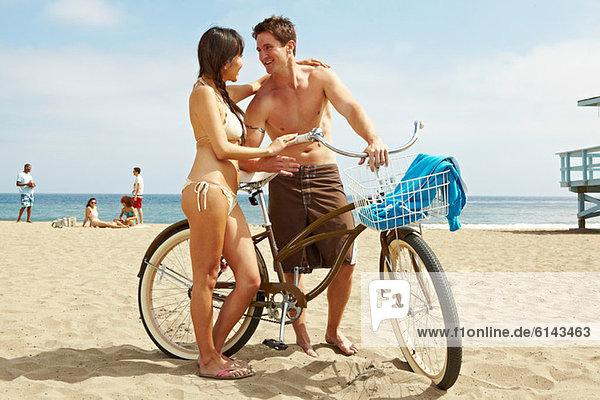 Junges Paar am Strand mit Fahrrad