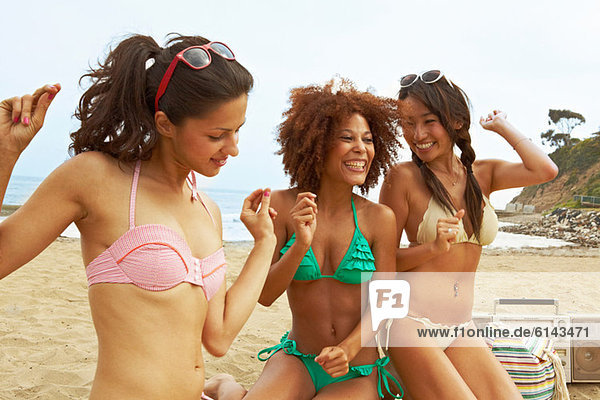 Junge Frauen am Strand mit Stereoanlage