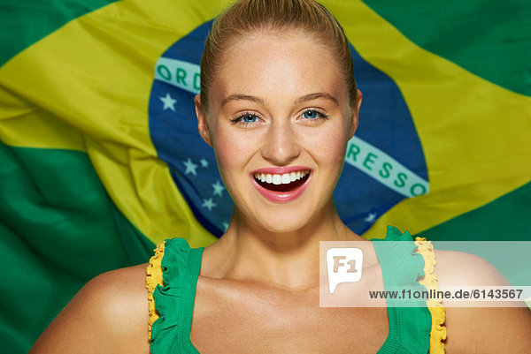 Junge Frau vor brasilianischer Flagge