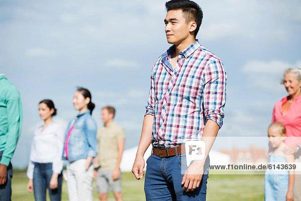 Junger Mann  der vor einer Gruppe von Menschen im Freien steht.