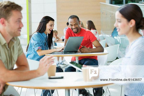 Junges Paar im Kantinenbereich  Blick auf Laptop