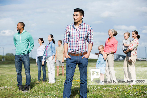 Young man standing in front of group of people outdoors