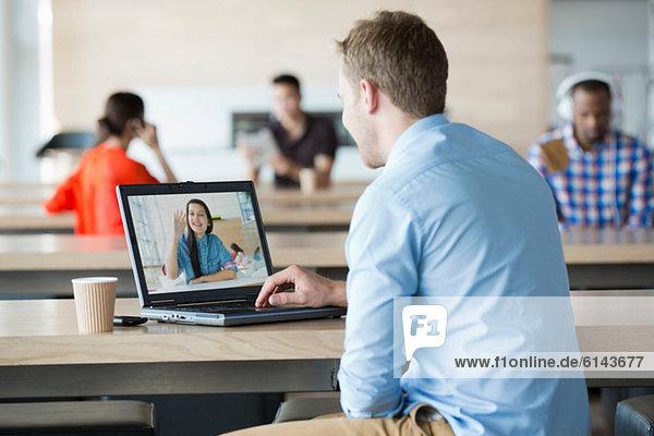 Junger Mann mit Laptop für Videoanrufe mit Freundin