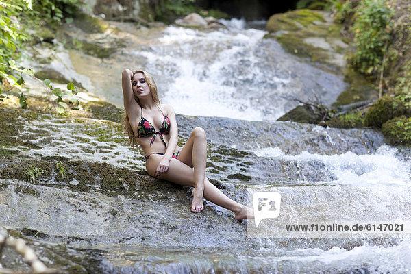 Junge Frau im Bikini posiert in einem Fluss