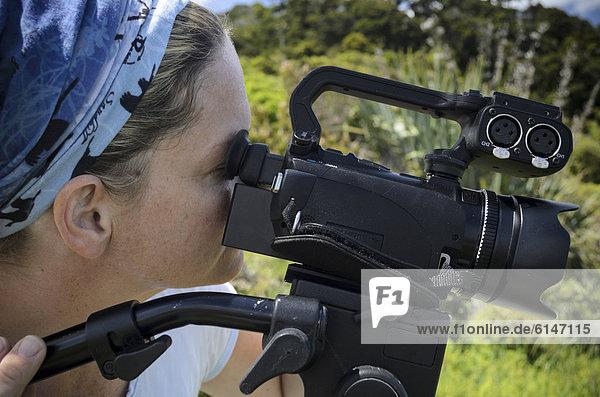 Junge Frau blickt durch den Sucher einer HD-Videokamera am Stativ  Neuseeland  Ozeanien