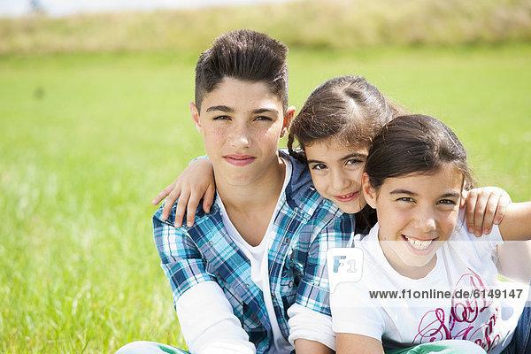 Drei Kinder sitzen auf einer Wiese