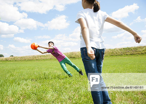 Two kids playing football on a meadow