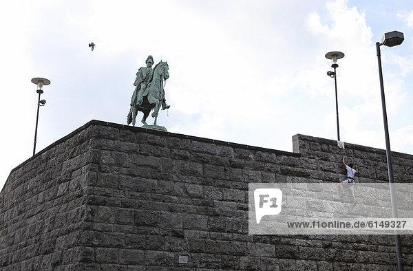 Kletterer an der Hohenzollernbrücke vor dem Kaiser Wilhelm Denkmal  Köln  Rheinland  Nordrhein-Westfalen  Deutschland  Europa