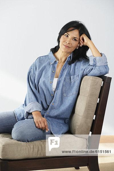 Hispanic woman sitting on chair
