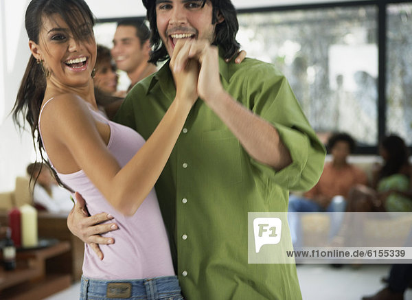 South American couple dancing at party