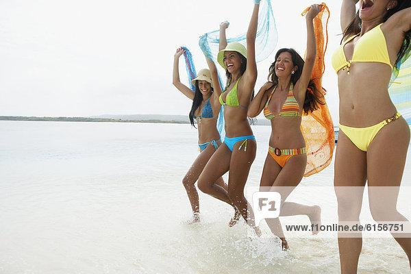 South American women jumping on beach