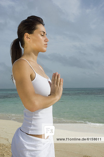 Frau üben Yoga am Strand