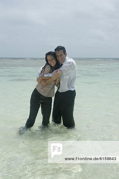 Hispanic businesspeople hugging in water
