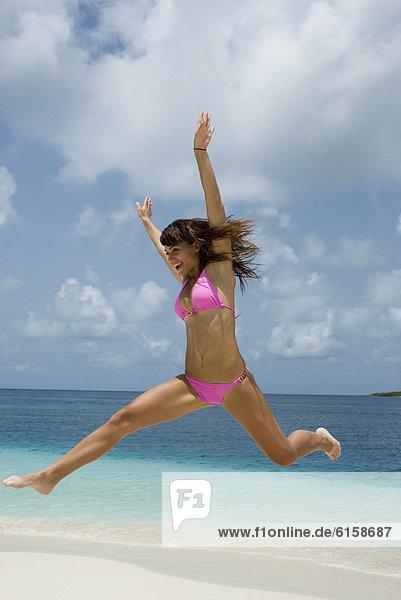Junge Frau am Strand springen
