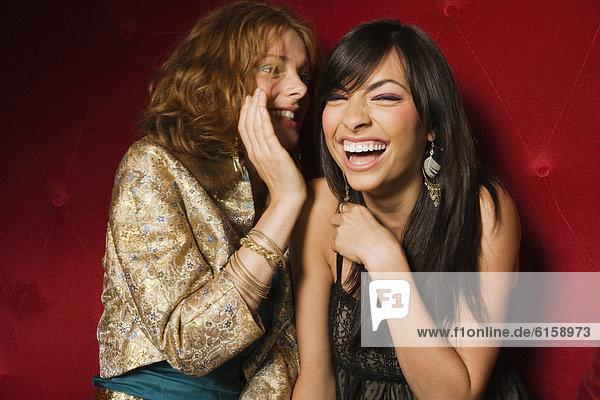 Multi-ethnic women telling secret