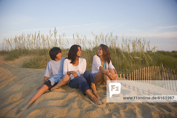 Asian woman and children sitting on beach