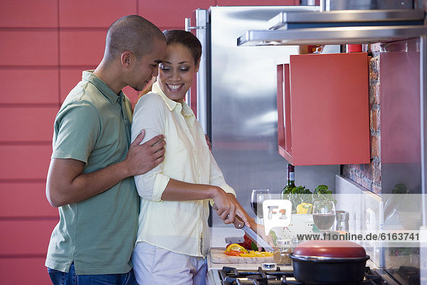 African American couple hugging in kitchen