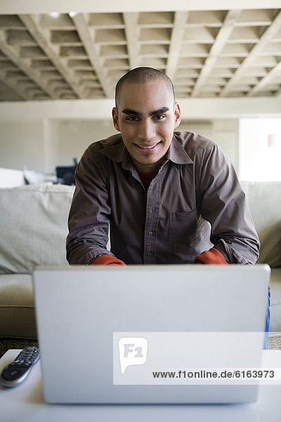 African American man sitting behind laptop