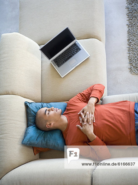 African American man sleeping on sofa