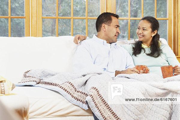 sitzend Zusammenhalt Decke unterhalb Couch