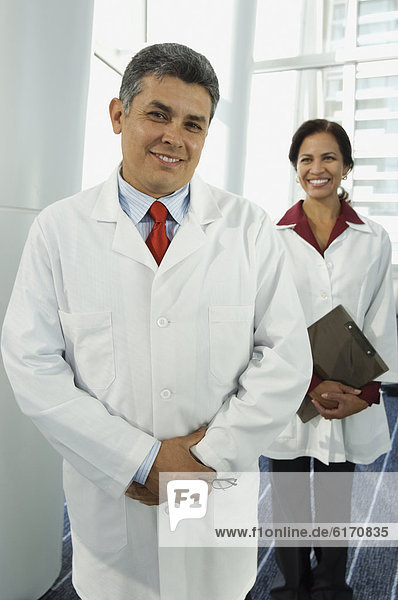Hispanic male doctor with female doctor in background