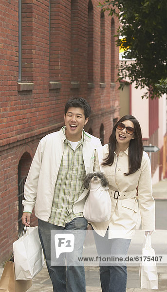 Young Asian couple walking down the sidewalk with shopping bags