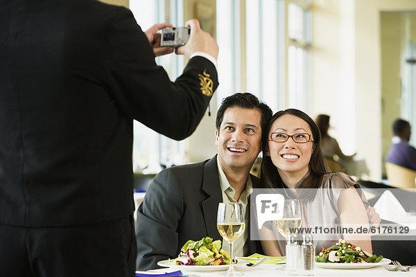 Couple having photograph taken at restaurant