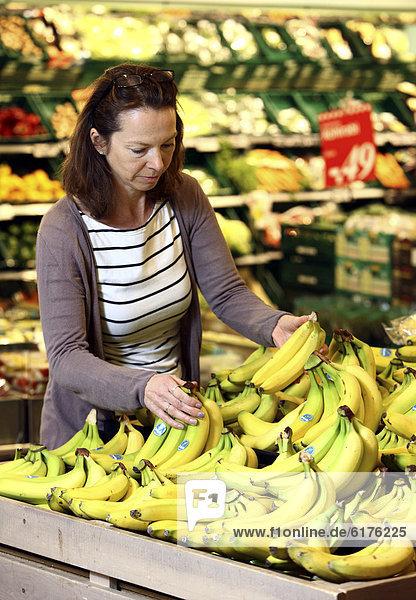 Obstabteilung  Frau kauft Bananen ein  Selbstbedienung  Lebensmittelabteilung  Supermarkt  Deutschland  Europa