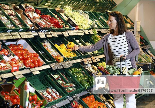 Frau kauft in der Gemüseabteilung ein  Selbstbedienung  Deutschland  Europa