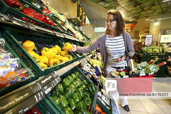 Frau kauft in der Obst- und Gemüseabteilung ein  Selbstbedienung  Lebensmittelabteilung  Supermarkt  Deutschland  Europa