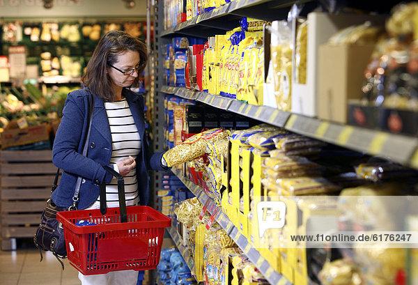 Frau kauft Nudeln  Pasta ein  Selbstbedienung  Lebensmittelabteilung  Supermarkt  Deutschland  Europa