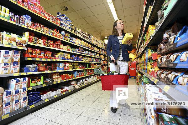 Frau kauft Kaffeepads ein  Selbstbedienung  Lebensmittelabteilung  Supermarkt  Deutschland  Europa