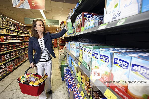Frau kauft Sojamilch ein  Selbstbedienung  Lebensmittelabteilung  Supermarkt  Deutschland  Europa