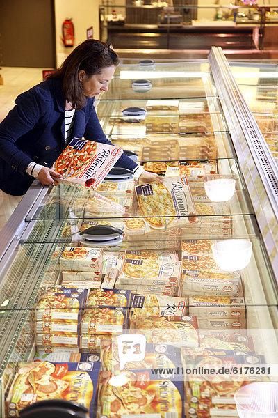 Frau beim Einkauf von Tiefkühl-Pizza  Tiefkühlabteilung  Lebensmittelabteilung  Selbstbedienung  Supermarkt  Deutschland  Europa