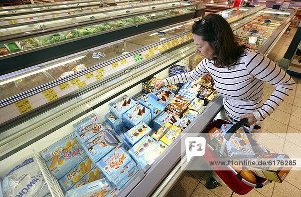 Frau kauft Eis ein  Tiefkühlabteilung  Lebensmittelabteilung  Selbstbedienung  Supermarkt  Deutschland  Europa
