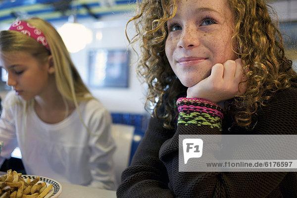 Caucasian girls eating in cafe