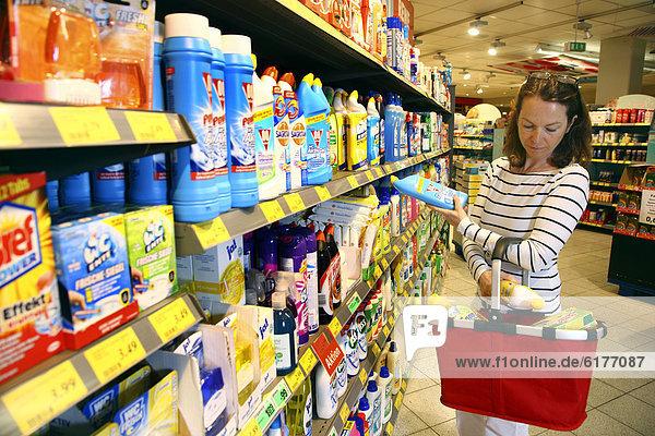 Frau betrachtet Produkte an einem Regal mit Reinigungsmitteln  Haushaltswaren  Selbstbedienung  Supermarkt  Deutschland  Europa
