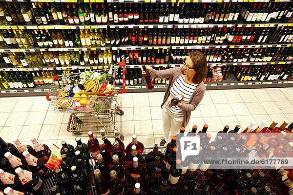 Frau beim Einkaufen in Getränkeabteilung  Sekt  Champagner  Schaumweine  Regal  Selbstbedienung  Deutschland  Europa