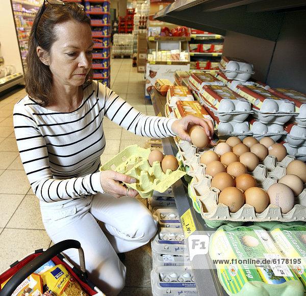 Frau kauft lose Hühnereier aus Freilandhaltung  Selbstbedienung  Lebensmittelabteilung  Supermarkt  Deutschland  Europa