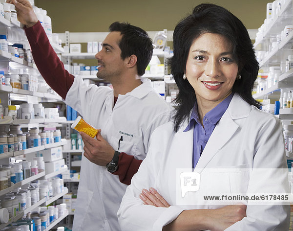 Asian pharmacist in front of coworker