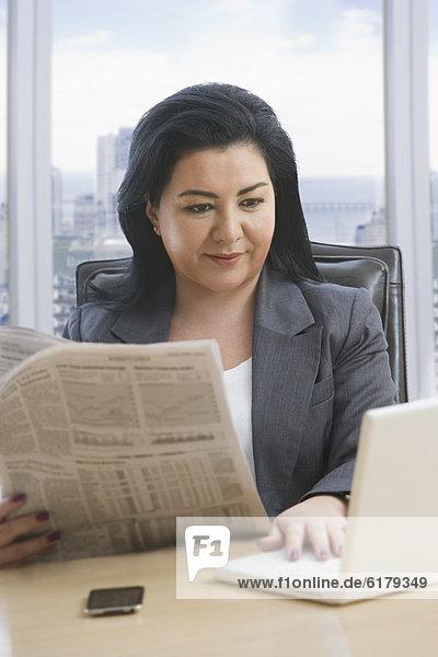 benutzen  Geschäftsfrau  Notebook  Hispanier  Zeitung  vorlesen